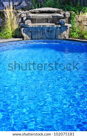 Outdoor inground residential private swimming pool with waterfall - stock photo