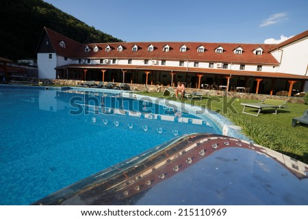 Outdoor inground residential swimming pool in backyard with hot tub  - stock photo