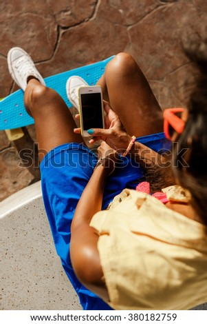 Outdoor lifestyle close-up of black sporty lady in bright outfit and sunglasses. Young hipster girl sitting at skate park and chatting on her smartphone. She is happy. Sunny summer day. Swag, fashion. - stock photo