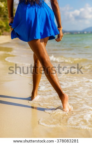 Outdoor lifestyle close-up of long beautiful legs of a sporty black teenage girl at tropical seashore. Closeup detail of female feet, water splash and golden sand. Young hipster, sunny hot summer day. - stock photo