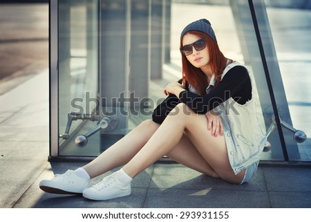 Outdoor lifestyle fashion portrait of pretty young sitting girl, wearing hipster swag grunge style urban background. Red hair. Retro vintage toned image, film simulation. - stock photo