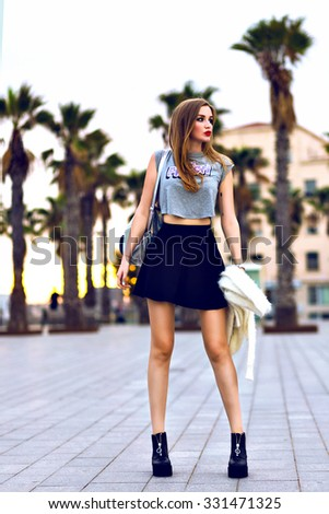 Outdoor lifestyle fashion portrait of young hipster woman walking at Barcelona, travel with backpack, stylish casual outfit, evening sunset, palms, student, bright make up bf hairstyle, happy time. - stock photo