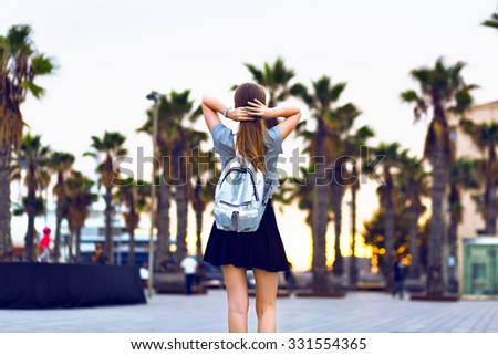 Outdoor lifestyle fashion portrait of young hipster woman walking at Barcelona, travel with backpack, stylish casual outfit, evening sunset, palms, student, blonde hairstyle, happy time, toned colors. - stock photo