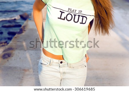Outdoor lifestyle hipster teen girl posing alone,wear cool designer t-shirt,with music icon.Warm vintage bright colors.toned,T -shirts with prints,bright T-shirt with the words,Printed,youth jersey - stock photo