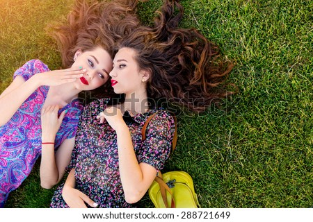 Outdoor lifestyle  image of two best friends in colorful boho dress and curly hair  laying on the green grass and talking about. - stock photo