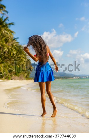 Outdoor lifestyle of a sporty black teenage girl with long beautiful legs at tropical seashore. Close-up detail of female feet, water splash and golden sand. Young hipster, sunny hot summer day. - stock photo