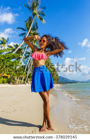 Outdoor lifestyle portrait of black teenage girl in pink bra and blue skirt. Young hipster woman correct her pink sunglasses. Sunny hot summer day at tropical beach with palms. Happy lady life.