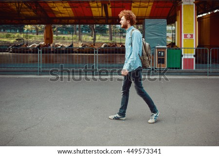 Outdoor lifestyle portrait of handsome ginger guy with backpack