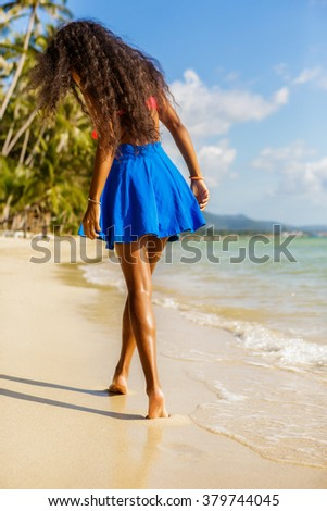 Outdoor lifestyle portrait of long beautiful legs of a sporty black teenage girl at tropical seashore. Closeup detail of female feet, water splash and golden sand. Young hipster, sunny hot summer day. - stock photo