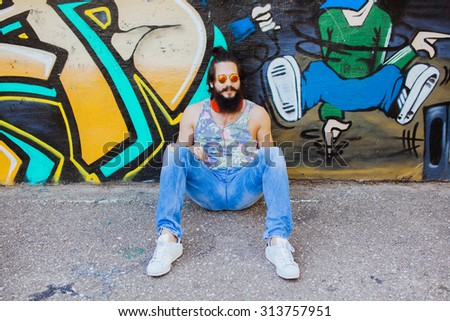 Outdoor lifestyle portrait of man smiling and listen music.boy posing on the wall,ready to trip.Happy and active.mans hairstyle.trendy man sunglasses,Young sportsman,young dj,t-shirt and shorts, - stock photo