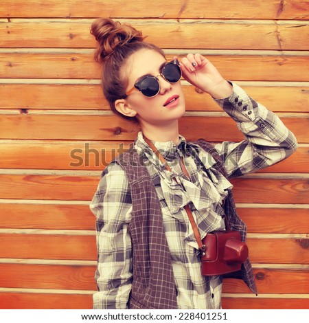 Outdoor lifestyle portrait of pretty funny hipster woman making photo. Retro photographer. Modern urban girl has fun with vintage photo camera, wooden background. Photo toned style Instagram filters. - stock photo