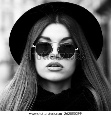 Outdoor lifestyle portrait of pretty funny hipster woman. Modern urban girl having fun. Beautiful young girl in a hat. Black and white portrait. - stock photo