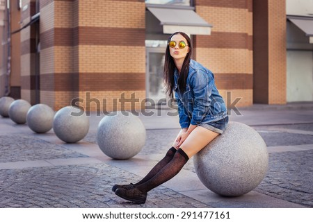 Outdoor lifestyle portrait of pretty young girl, wearing in hipster swag grunge style urban background. Retro vintage toned image, film simulation. - stock photo