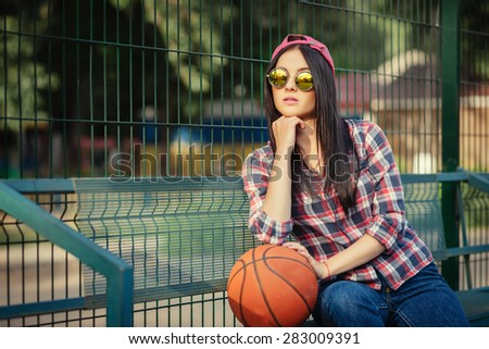 Outdoor lifestyle portrait of pretty young girl, wearing in hipster swag grunge urban style and creative sunglasses. Basketball court and orange ball. Retro vintage toned image, film simulation. - stock photo