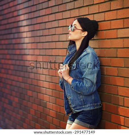 Outdoor lifestyle portrait of pretty young sitting girl, wearing in hipster swag grunge style in urban background. Retro vintage toned image, film simulation. - stock photo