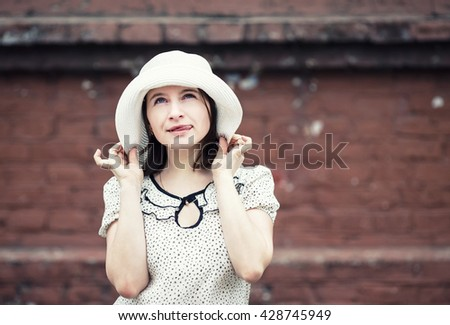 Outdoor lifestyle portrait of pretty young woman in white hat on brick wall background. Girl posing and showing tongue. Vintage style photo. Toned photo with copy space. - stock photo