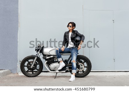 Outdoor lifestyle portrait of sexy biker woman sitting on a vintage custom motorcycle