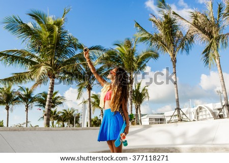 Outdoor lifestyle portrait of smiling black young woman in bright outfit. Hipster girl with penny skateboard taking selfie self portrait on her smartphone digital camera. Sunny hot day. Swag, fashion. - stock photo