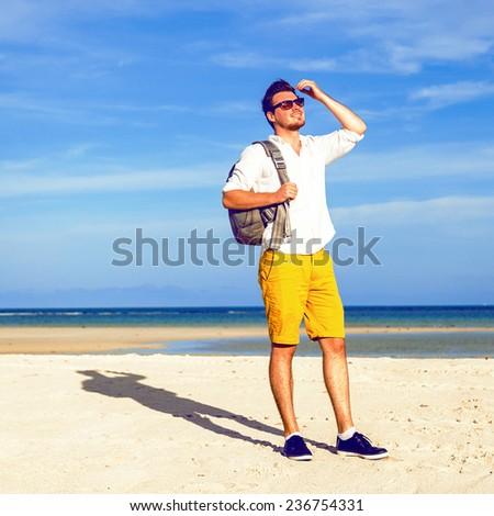 Outdoor lifestyle portrait of traveler backpacker stylish hipster man enjoying hot sunny summer day at amazing beautiful beach. - stock photo