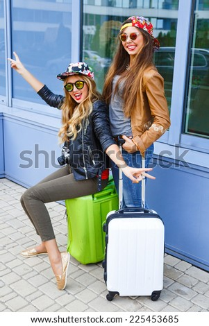 Outdoor lifestyle portrait of two pretty sisters ready for travel, posing with luggage near airport, having fun and making crazy funny faces, wearing bright trendy casual clothes. - stock photo