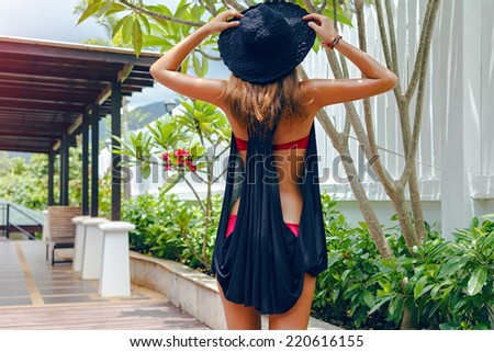 Outdoor lifestyle portrait of woman relaxed at resort on her vacation in hot tropical county, posing at exotic garden, wearing hat, bikini, and black cover. - stock photo