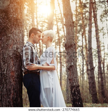 Outdoor lifestyle portrait of young couple hugging in pine forest. Sunny warm weather. Backlight and sun. Retro vintage toned image, film simulation. - stock photo