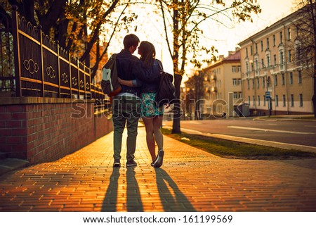 Outdoor lifestyle portrait of young couple in love standing in old town on the street behind sunset - stock photo
