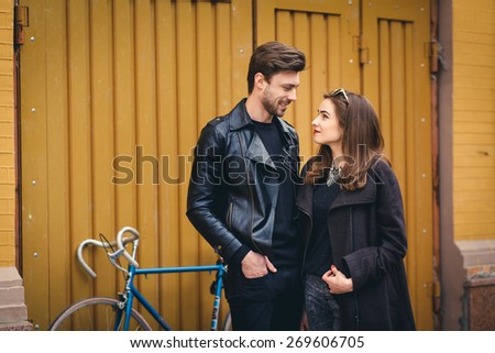 Outdoor lifestyle portrait of young couple in love standing in old town on the street, bike, hipsters, - stock photo