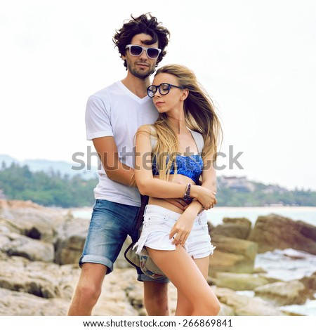 Outdoor lifestyle portrait of young pretty hipsters couple in love, posing at amazing beach, vintage toned colors, summer style. - stock photo