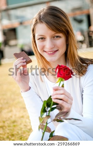 Outdoor lifestyle portrait of young woman eating chocolate with red rose - stock photo