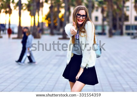 Outdoor lifestyle portrait posing with backpack after studying, walking on  embankment, palms and sunset on background, trendy hipster outfit. showing ok science