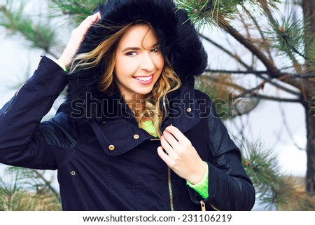 Outdoor lifestyle winter portrait of pretty smiling woman posing near fir tree in front of snow , wearing trendy parka and neon sweater. Bright colors happy holidays mood. - stock photo