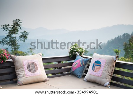outdoor living room with pillows  - mountain and forest background - stock photo