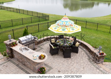Outdoor living space on a brick patio overlooking a tranquil lake and fenced green lawn with a table under a sunshade or umbrella laid ready for dinner, high angle view - stock photo