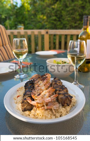 Outdoor meal with chicken and shrimp brochette on the rice. Alcohol white wine. Very shallow depth of field. - stock photo