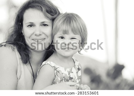 Outdoor monochrome portrait of a real Caucasian family, young mother with her small cute daughter  - stock photo