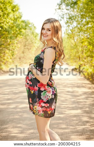 Outdoor natural portrait of beautiful smiling  pregnant woman - stock photo
