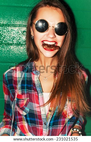 Outdoor night closeup lifestyle urban style portrait of pretty young beautiful girl with smile and chocolate in her mouth with red lipstick having fun  - stock photo