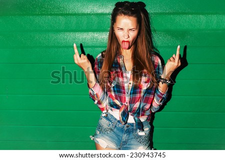 Outdoor night fashion urban portrait of young sexy pretty brunette spoiled crazy girl showing tongue and middle finger gesture on green background  - stock photo