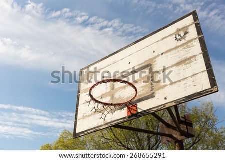 Outdoor old basketball hoop with blue sky and clouds - stock photo