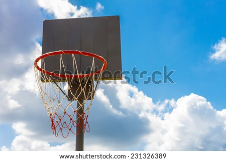 Outdoor old wood basketball hoop with blue sky and clouds background - stock photo