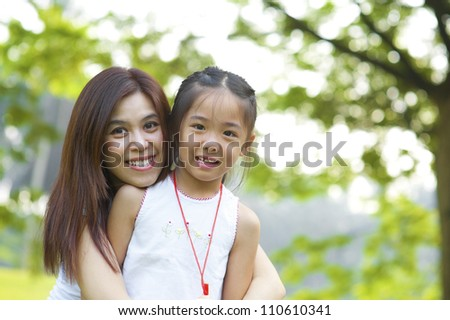 Outdoor park happy Asian mother and daughter - stock photo