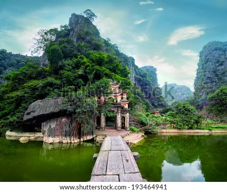 Outdoor park landscape with lake and stone bridge. Gate entrance to ancient Bich Dong pagoda complex. Ninh Binh, Vietnam travel destination - stock photo