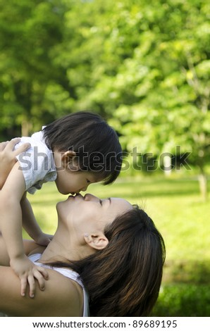 Outdoor park mother kissing son - stock photo