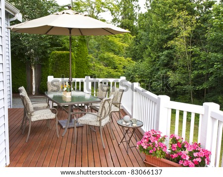 Elegant Outdoor Patio Setup On Cedar Wood Deck With Trees In Background