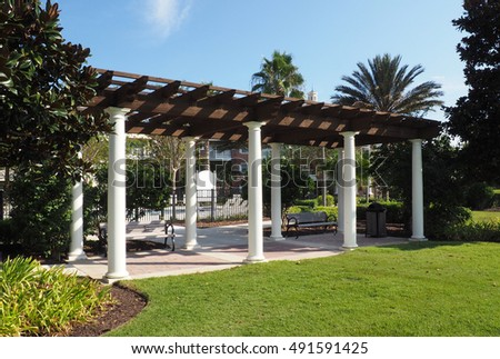 outdoor pavilion with a wood roof and columns.  There are benches under the pavilion and it is surrounded by lush vegetation