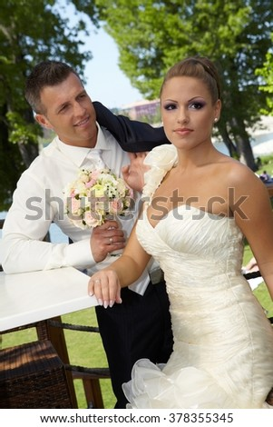 Outdoor photo of attractive young couple on wedding day. - stock photo