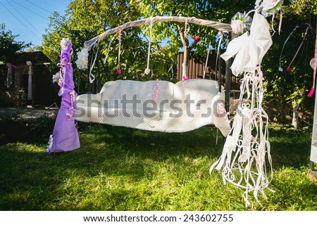 Outdoor photo of beautiful decorated for wedding swing at backyard - stock photo