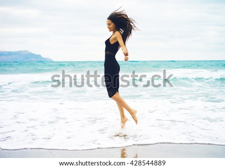 Outdoor photo of beautiful young woman jumping at the sea - stock photo