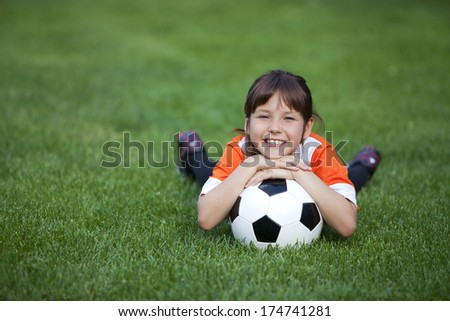 Outdoor photo of cute little girl leaning on soccer ball in green grass - stock photo
